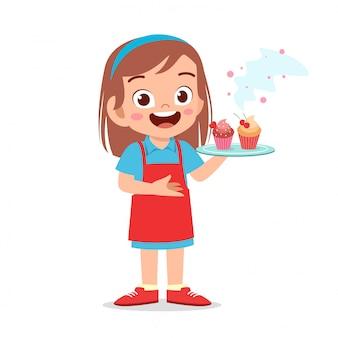 Happy cute kid girl try cooking cupcake