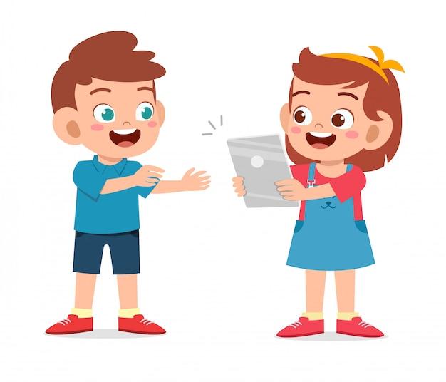 幸せなかわいい子供の友人にタブレットを共有