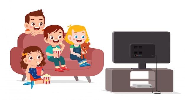 幸せなかわいい子供は家族と一緒にテレビを見る