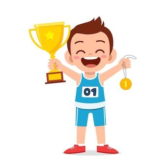 Счастливый милый маленький мальчик держит золотую медаль и трофей