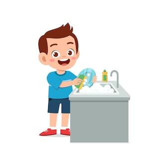 キッチンでお皿を洗う幸せなかわいい男の子