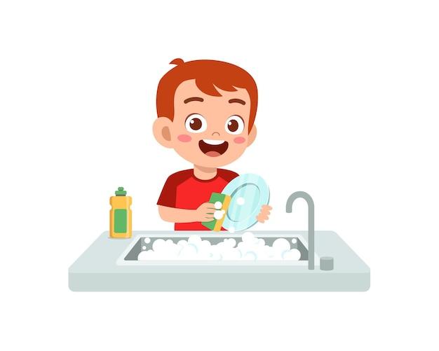 Счастливый милый маленький мальчик моет посуду на кухне