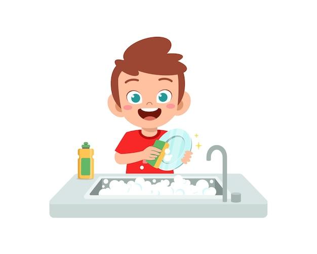 Happy cute little boy washing dish in the kitchen