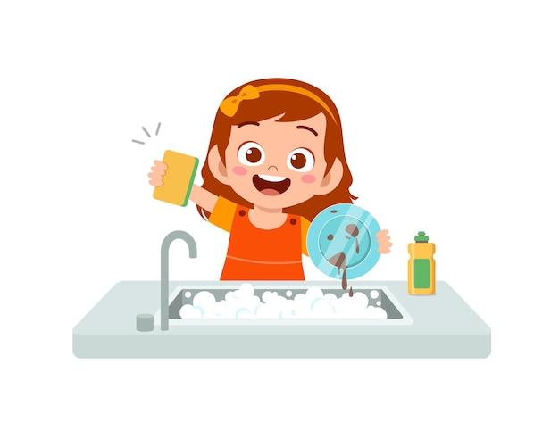 幸せなかわいい女の子が台所で皿を洗う