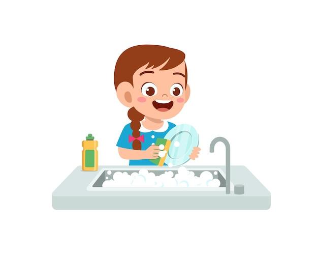Счастливая милая маленькая девочка моет посуду на кухне