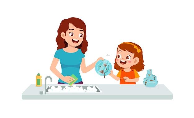幸せなかわいい女の子が母親と一緒に皿を洗う