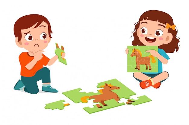 Счастливый милый маленький мальчик и девочка играют в пазл