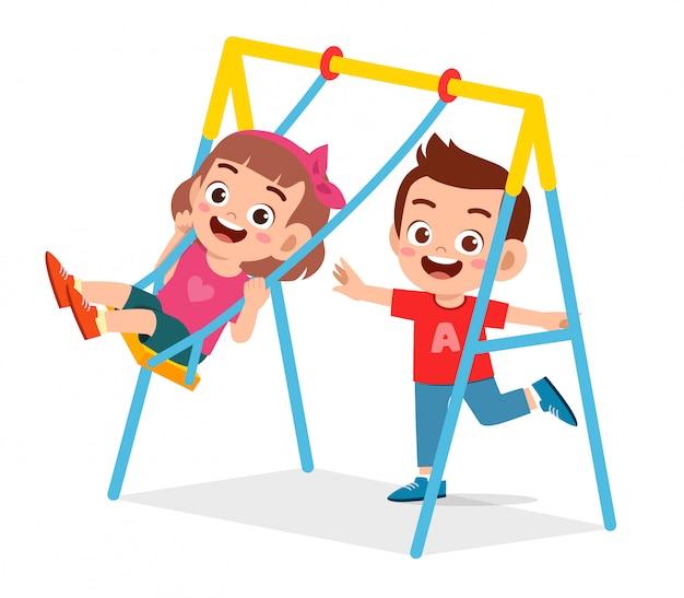 幸せなかわいい子供男の子と女の子の遊びスイング