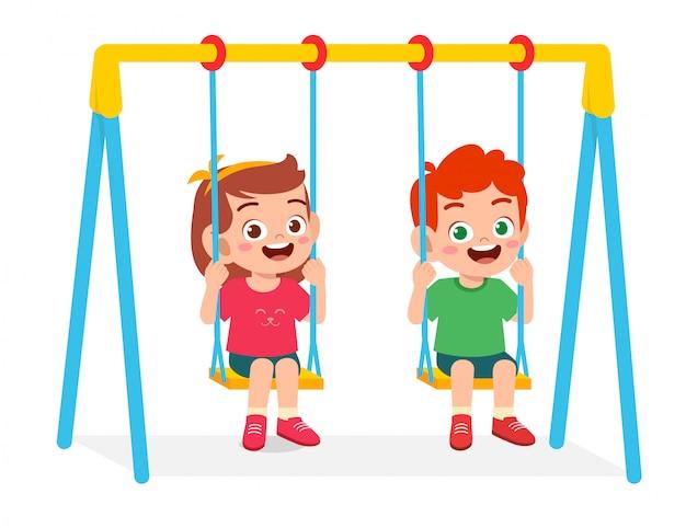 Счастливый милый маленький мальчик и девочка играют качели