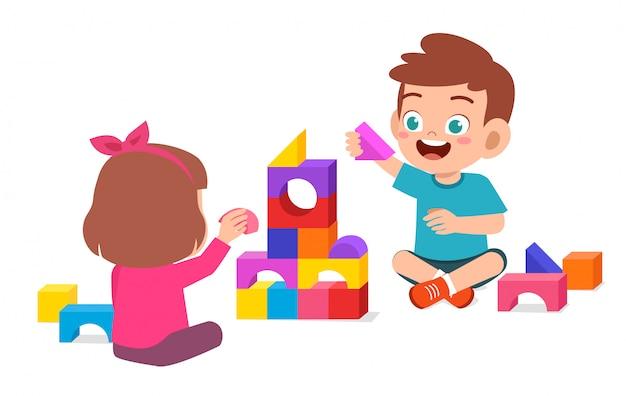 Счастливый милый маленький мальчик и девочка играют вместе