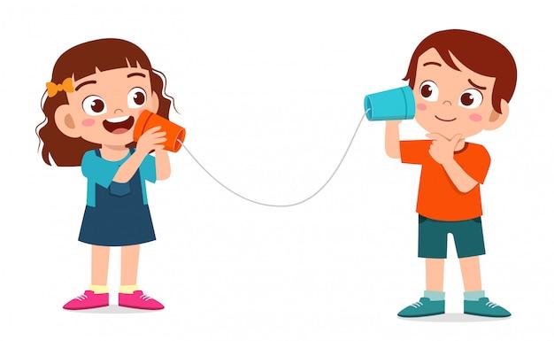 Счастливый милый маленький мальчик и девочка играют игрушечный телефон