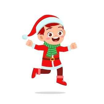 Счастливый милый маленький ребенок мальчик и девочка в красном рождественском костюме и прыгают