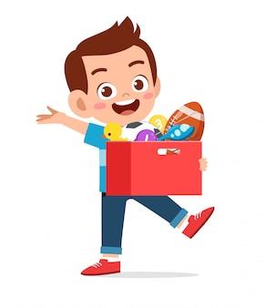 幸せなかわいい子供男の子はおもちゃの箱を運ぶ