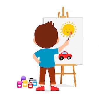 Happy cute little kid boy draw on canvas