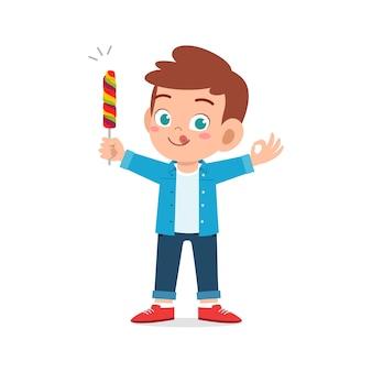 幸せなかわいい小さな子供の男の子はお菓子やお菓子を食べます
