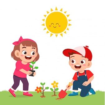 Happy cute little kid boy and girl plant flower
