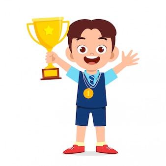 Happy cute little kid boy holding trophy