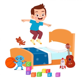 Happy cute little kid boy jump on bed
