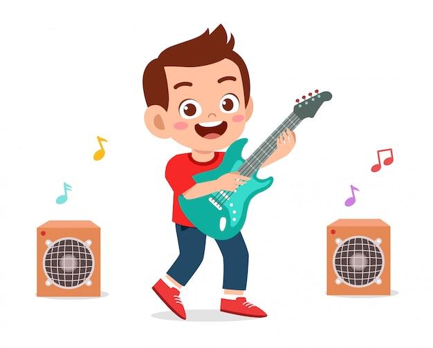 Happy cute little kid boy play guitar
