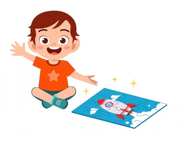 Happy cute little kid boy play jigsaw puzzle