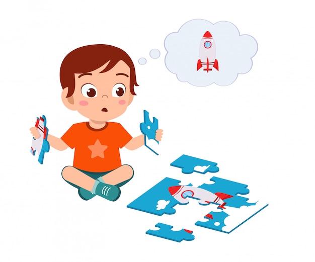 Счастливый милый маленький малыш мальчик играть в головоломки Premium векторы