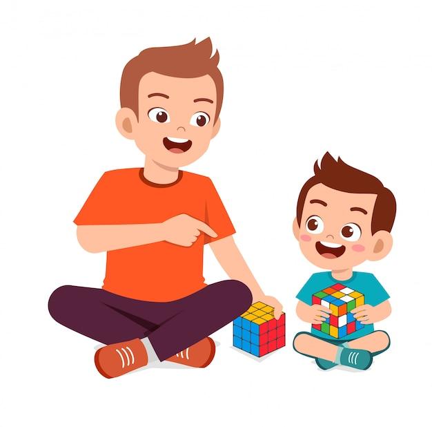 Happy cute little kid boy play rubik cube with dad