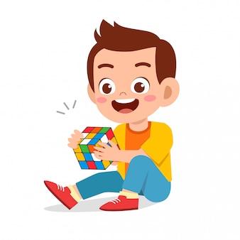 Happy cute little kid boy play rubik cube