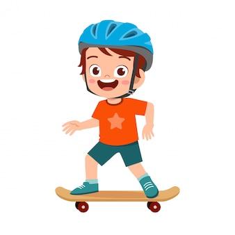 Happy cute little kid boy play skateboard