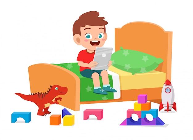 Счастливая милая игра мальчика маленького ребенка с таблеткой в комнате кровати