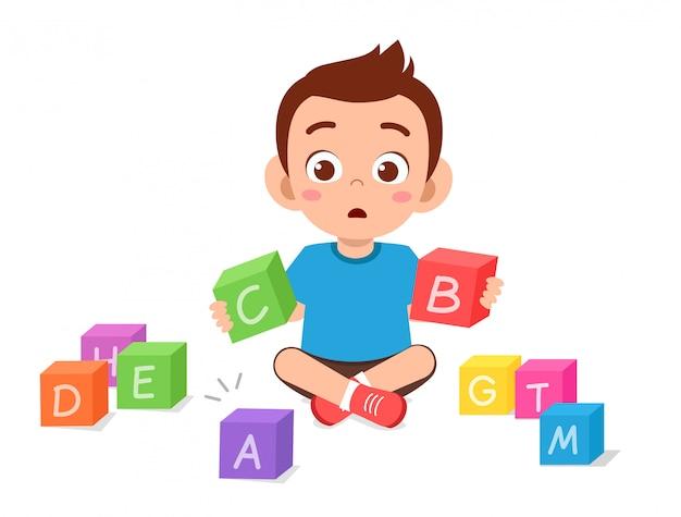 Счастливый милый маленький малыш мальчик играет блок