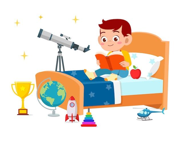 행복 한 귀여운 작은 아이 소년 침대 방에서 책을 읽고