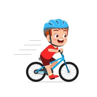 自転車に乗って幸せなかわいい小さな子供の男の子