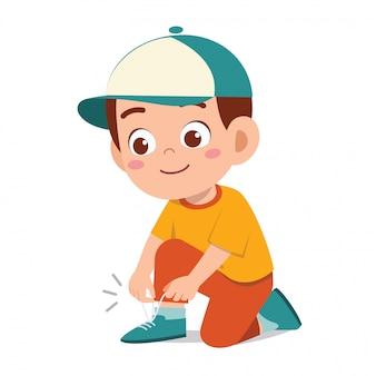 Счастливый милый маленький мальчик малыш завязывать шнурок
