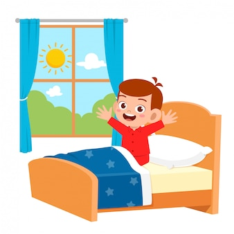 Happy cute little kid boy wake up in the morning