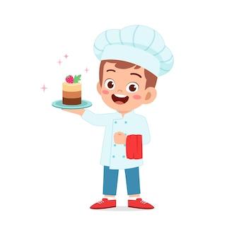 幸せなかわいい小さな子供の男の子は、シェフの制服を着て、バースデーケーキを調理します