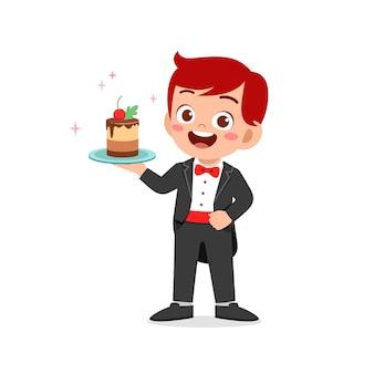 ウェイターの制服を着て、バースデーケーキを保持している幸せなかわいい男の子