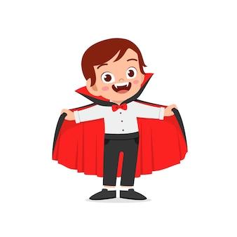 Happy cute little kid celebrate halloween wears dracula vampire costume with cape