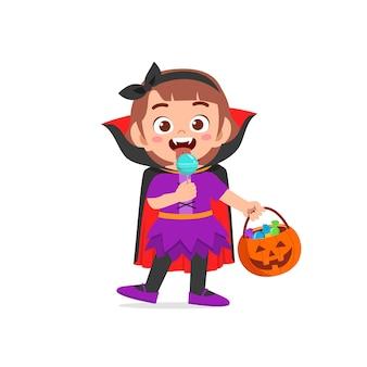ハロウィンを祝う幸せなかわいい子供はケープ付きドラキュラ吸血鬼の衣装を着ています