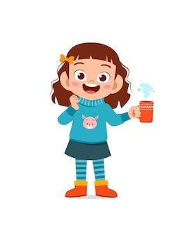 Счастливый милый маленький ребенок пьет горячий шоколад в зимний сезон