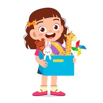 幸せなかわいい子供女の子はおもちゃの箱を運ぶ