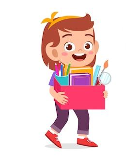 Happy cute little kid girl carry box of school supplies