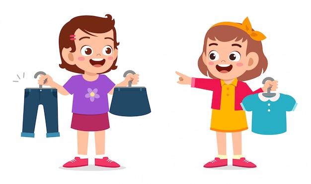 Счастливая милая маленькая девочка выбирает одежду