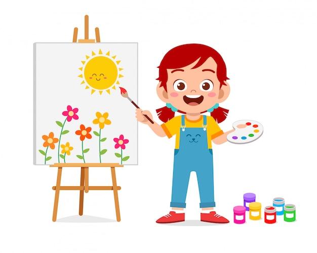 Счастливая милая маленькая девочка рисует на холсте