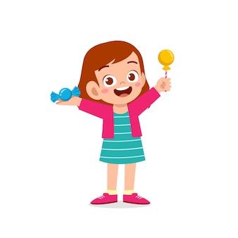 행복 한 귀여운 꼬마 소녀 사탕과 과자를 먹고