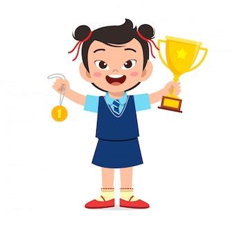Happy cute little kid girl holding trophy