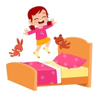 Happy cute little kid girl jump on bed room