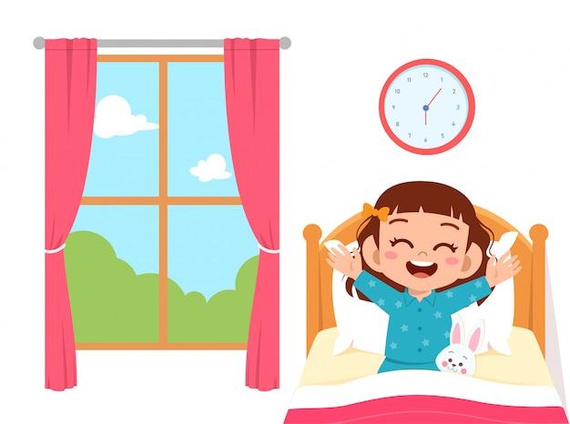 幸せなかわいい子供女の子が朝目を覚ます