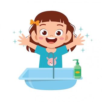幸せなかわいい子供女の子がシンクで手を洗う