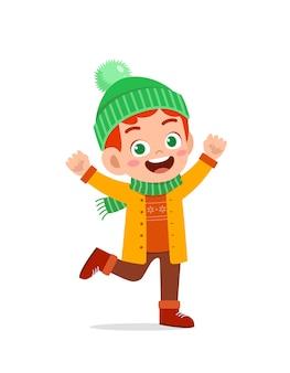 Счастливый милый маленький ребенок играет и надевает куртку в зимний сезон