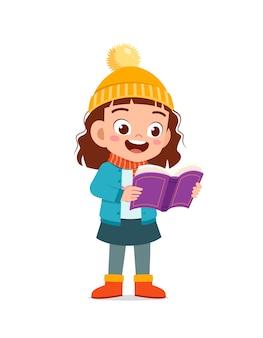 幸せなかわいい小さな子供は冬の季節に勉強してジャケットを着ます